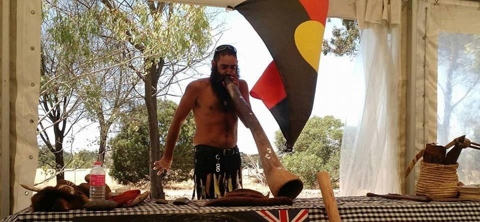 Aboriginal Man Norm Jurrawaa Stanley playing didjeridu on tour